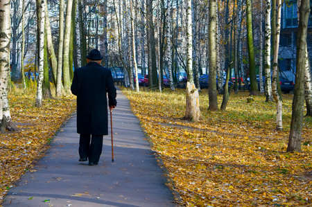 old man standing: back of walking old man with walkingstick Stock Photo