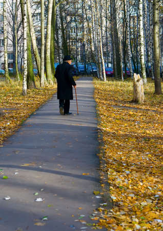 back of walking old man with walkingstick photo