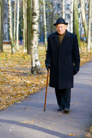 portrait of walking old man in a hat with walkingstick Stock Photo
