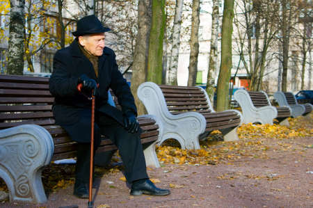 old elegant man with walkingstick sitting on a bench