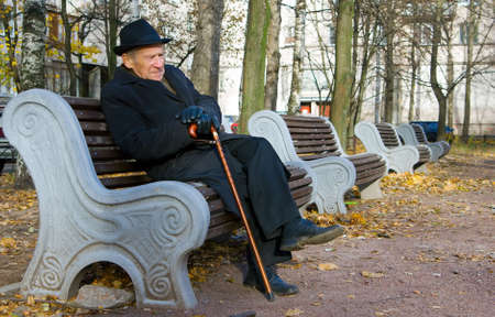 portrait of an old man in a hat sitting on a bench Stock Photo