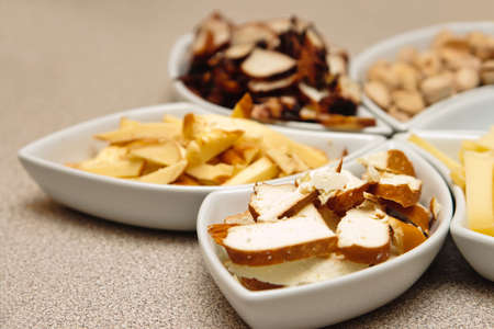 close-up beer snacks - cheese, bloated fish and squid, groundnuts photo