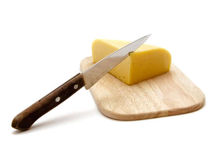 block of cheese on cutting board with a knife, slicing through it, isolated on white background photo