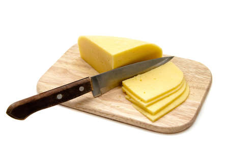 block of cheese with cut pieces on cutting board with a knife, isolated on white background photo