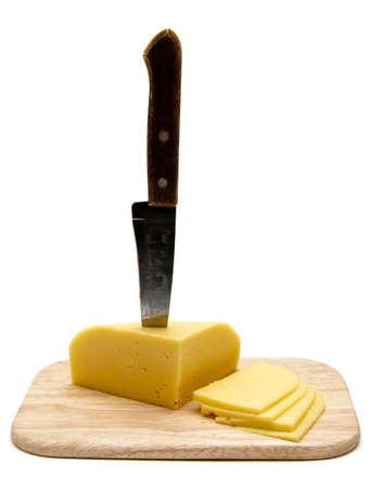 block of cheese with cut pieces on cutting board with a knife, slicing through it, isolated on white background photo
