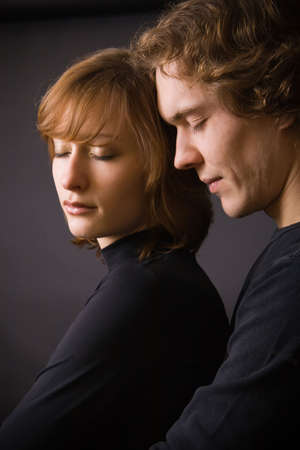portrait of black dressed loving couple with closed eyes, in studio Stockfoto