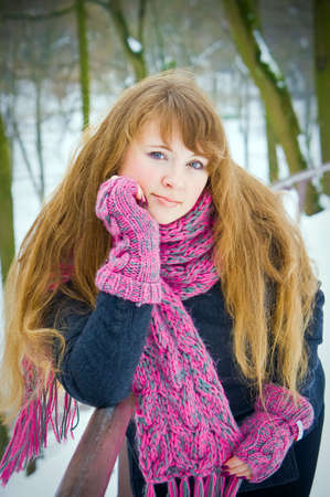 portrait of a young woman with long hair, she is in a winter pink scarf and gloves Stock Photo - 6535132
