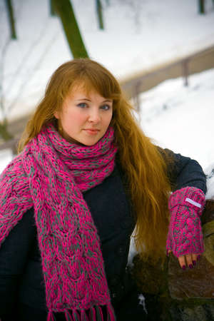 portrait of a young woman in winter pink scarf and gloves photo