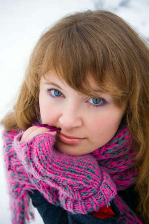 close-up portrait of a female in a winter pink scarf and gloves photo