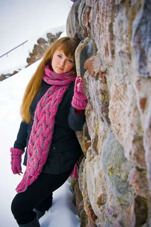 portrait of a young woman in pink scarf and gloves, she is standing near a stone wall Stock Photo - 6557370