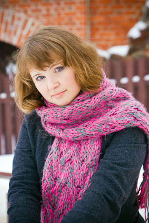 portrait of a young woman with pink scarf, she is standing in front of a fence Stock Photo - 6598017