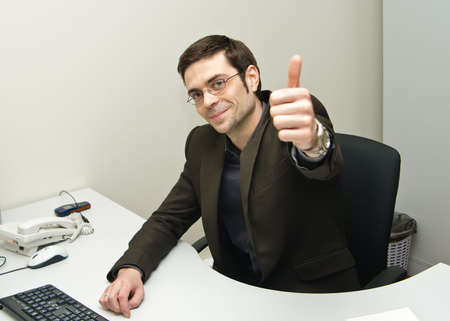 portrait of a joyful businessman in suit with his thumb up photo