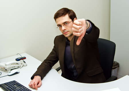 displeased businessman: portrait of a displeased serious businessman with his thumb down Stock Photo