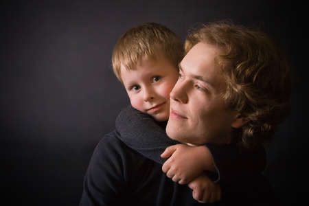 portrait of a beautiful couple in studio with black background - little son is putting his arms round his father photo
