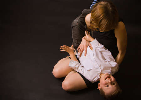 tickling: portrait of a family - mother holding her little son and tickling him, he is laughing