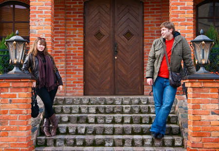 young couple standing on a steps near an old house with lamps, he is looking on her, she is looking straight and smiling Stock Photo - 6931524