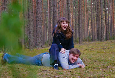 portrait of a cheerful laughing couple - he is lying on a grass and she is sitting on his back photo