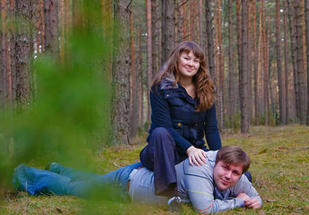 couple in the forest, they are playing the fool, she is sitting on his back - she is the winner photo