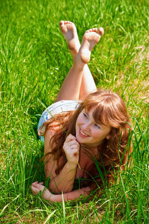 portrait of a beautiful female lying on a grass, it is summer and sun is shining, she is laughing Stock Photo - 7063708