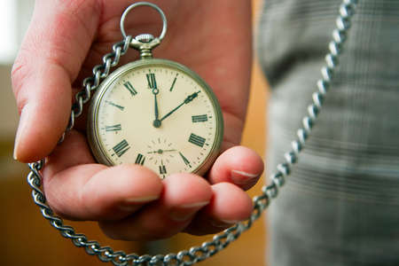 person holding old pocket watch in his hand photo