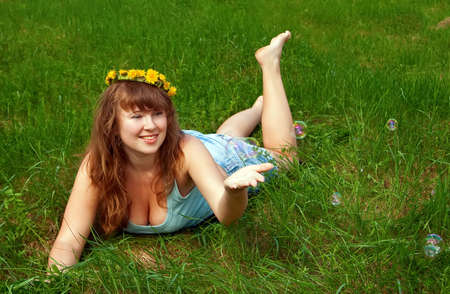 portrait of a beautiful female with a dandelions garland, it is summer and she is playing with soap bubbles photo