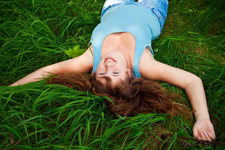 portrait of a beautiful happy female lying on a grass, it is summer and she is laughing Stock Photo - 7161445