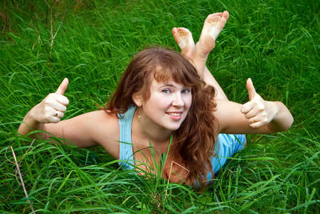 portrait of a beautiful female lying on a grass with her thumbs up, it is summer and she is smiling Stock Photo - 7161434