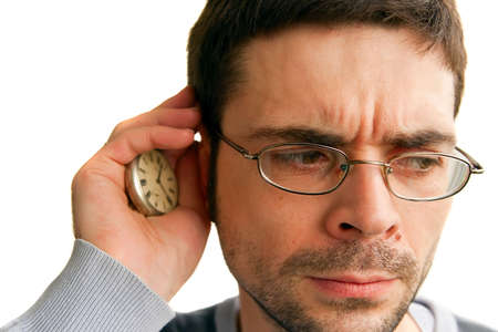 frowned: frowned man in glasses listening to ticking of his clock, isolated on white background Stock Photo