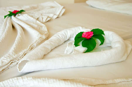 close-up decoration on a hotel rooms bed with flowers photo