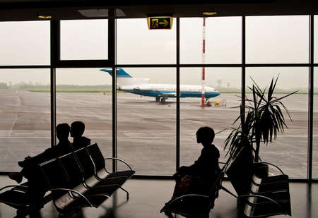 silhouettes of people sitting on chairs in the airport, in the window we can see the airplane