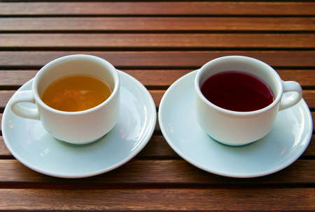 two white cups with different kinds of tea - red fruit and yellow