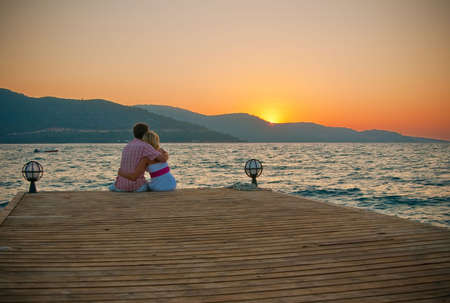 couple embracing each other while sitting on a pier and looking on a sunset in front of them
