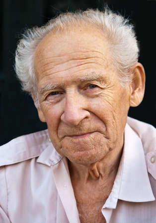 face portrait of a senior man on a black background