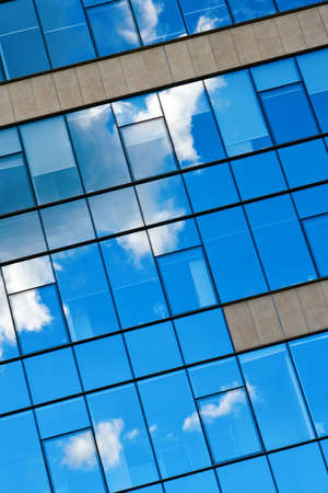 blue sky and clouds reflecting in the glass of an office building photo