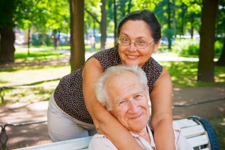 smiling mature couple enjoying fresh air in a park, they are different age, but they love each other