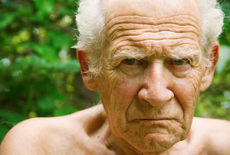 face portrait of an old angry frowning senior man