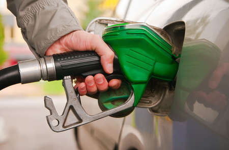 fill: male hand refilling the car with fuel on a filling station