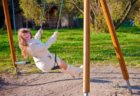 looking natural young laughing woman in white clothing, swinging photo