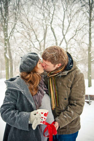 young pair kissing outdoors, it is winter and snowing, woman is pregnant, she is holding a cup with painted hearts Banque d'images - 8668225
