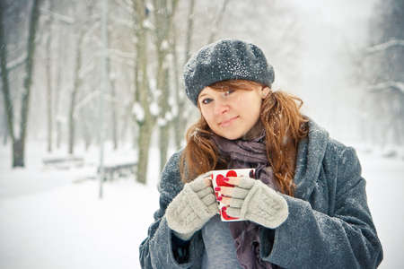 young woman holding a cup with painted hearts, it is winter and snowing Stock Photo - 8668174