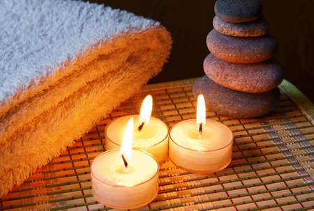 close-up three burning candles, gray stones and cotton towel on a bamboo napkin  photo