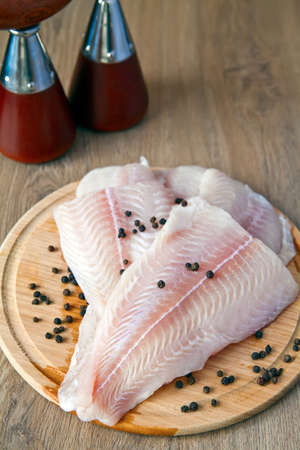 pangasius: raw fish pangasius with black pepper on a wood board