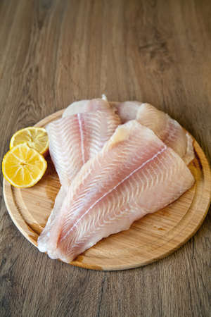 whitefish: raw fish pangasius with lemon on a wood board Stock Photo