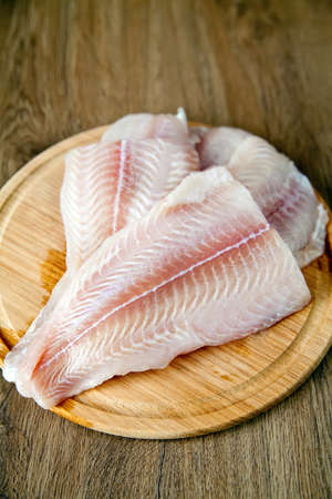 raw fish pangasius on a wood board photo