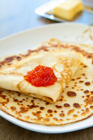 close-up pancake with salmons red caviar photo