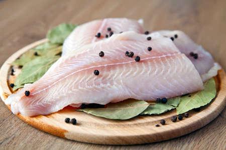 pepe nero: pangasius Close-up pesce crudo con pepe nero e foglie di alloro su una tavola di legna Archivio Fotografico