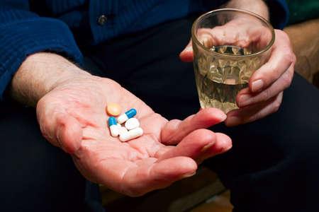 pills in hand: manos del anciano primer plano con p�ldoras y vaso de agua, que va a tomar un medicamento Foto de archivo