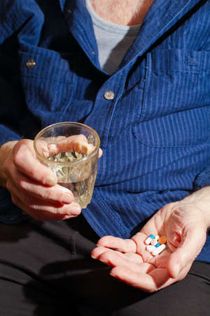 old man holding pills and glass of water in his hands, he is going to take some medicine Stockfoto