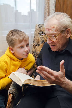 grandfather reading book aloud to his grandson, who is listening to him with attention Stock Photo