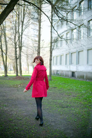 attractive woman in red coat walking her way, she is turning and smiling